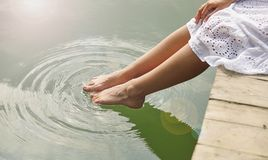 Women`s feet in the water. Plunges feeling freshness Royalty Free Stock Photos
