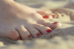 Women's feet wet in the sea sand Royalty Free Stock Image