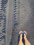 Women`s feet in white and blue sandals on the sand stock images