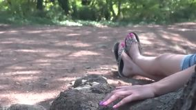 Women`s feet who relaxing under a big tree at sunset stock video footage