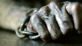 Women's fingers with dirty fingernails and burned skin. female hand shackled. Rusty chain. halloween stock video
