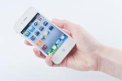 Women's fingers keeps White iphone 4. Women's fingers with a manicure keeps White iphone 4 on a white Stock Image