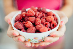 Women's fingers taken from the plate raspberries. Women's fingers with pink manicure taken from the plate raspberries Royalty Free Stock Photography