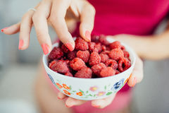 Women's fingers taken from the plate raspberries. Women's fingers with pink manicure taken from the plate raspberries Stock Photos