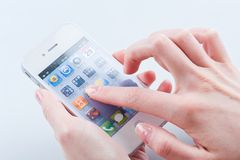 Women's fingers with white iphone 4 4s. Women's fingers with a manicure keeps White iphone 4 4s on a white Royalty Free Stock Image
