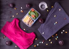 Women`s fitness collage. Several items for fitness sports bra and leggings, lunchbox with spinach, cheese and bread, a glass of water, plums and sweets stock photo