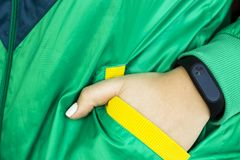 Women`s fitness - water and smart watches - gadgets and equipment for sports. Female hand with a fitness bracelet. In a sports bright green jacket for sports Stock Photos