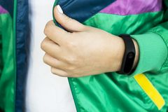 Women`s fitness - water and smart watches - gadgets and equipment for sports. Female hand with a fitness bracelet. In a sports bright green jacket for sports Stock Image