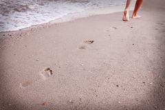 Women's footprints in the sand Stock Photo