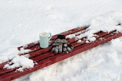 Women`s gloves and blue a mug on a bench among the snow. Nobody in a frame.  Royalty Free Stock Photos