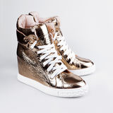 Women's gold sneakers Royalty Free Stock Photography