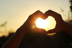 Women& x27; s-händer korsas i form av hjärtan till och med som sun&en x27; strålar gör vägen på solnedgången Arkivbild