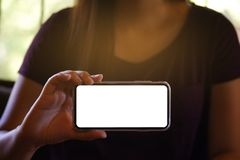 Women& x27; s-händer som framåtriktat rymmer den tomma skärmen för mobiltelefon för kopieringsutrymmeskärm smart telefon med tekn royaltyfri foto