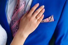 Women's hand on the chest of a man in an expensive suit. A close-up shot of a man in a blue suit while a woman�s hand is resting royalty free stock photo