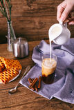Women`s hand with creamer pouring milk in glass with coffee. Cinnamon sticks, homemade cookies and bunch of wildflowers Stock Image
