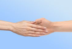 Women's hand goes to the man's hand. On blue background Royalty Free Stock Images