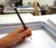 Women's hand grip a pencil writing on the white paper Stock Image