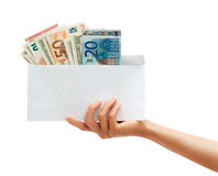 Women's hand holding out an envelope full of euro and dollars money Royalty Free Stock Photos