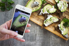 Women`s hand holding phone and taking photo of Sandwich with avo Royalty Free Stock Images