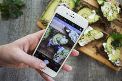 Women`s hand holding phone and taking photo of Sandwich with avo Stock Photos