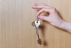 Women's hand holding two keys from the apartment. Wooden background Royalty Free Stock Image