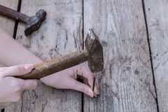 Women`s hand is keep hammer and to drive a nail is lying on a black wooden table. Copy space stock photo