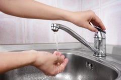 Women's hand opening water tap Stock Photo