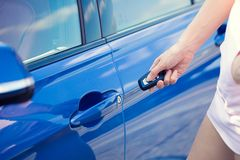 Women's hand presses on remote control unlocks car door. Cropped closeup image women's hand presses on remote control unlocks car door alarm systems. Vehicle stock images