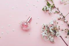 Women`s hand spray perfume. Flower arrangement. Flowers, fragrance, perfume on pink background.  royalty free stock photography