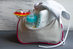 Women's handbag with items to care for the child: bottle of milk, disposable diapers, rattle, Stock Photos