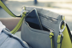 Women's handbag with the phone. On the street close up Royalty Free Stock Photography