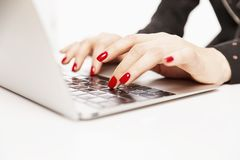 Women`s hands with a beautiful bright manicure on the keyboard of a stylish laptop, close-up stock images
