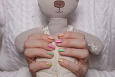 Women`s hands with a beautiful color manicure and soft toy royalty free stock images