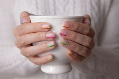 Women`s hands with a beautiful color manicure and white ceramic cup stock photos