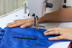 Women`s hands behind her sewing blue Stock Photo