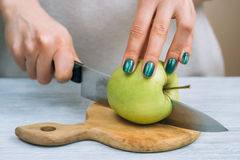 Women's hands with a bright manicure cut green apple with a kitc Stock Images