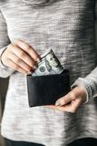 In the women`s hands is the leather wallet with a wad of hundred dollars. Business offer. Beautiful manicure Stock Photo