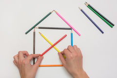Women`s hands are building house from pencils Royalty Free Stock Photo