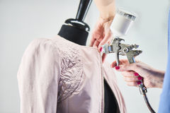Women's hands carry out the process of painting a leather jacket on the mannequin Royalty Free Stock Photography