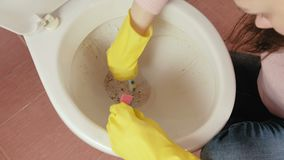 Closeup woman`s hands in yellow rubber gloves wash the toilet with sponge. Top view. Women`s hands close - up in yellow rubber gloves wash the toilet with stock footage