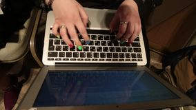 Women's hands with color nail polish typing on computer. RUSSIAN keyboard stock footage