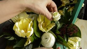 Women`s hands correct flowers in a bouquet.  stock footage