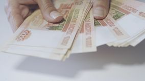 Women`s hands count Russian money in denominations of 5000.  royalty free stock photo