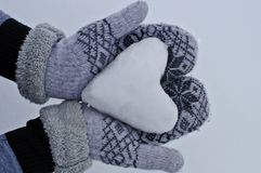 Women`s hands in cozy warm mittens keep the heart out of the snow against the background of snow royalty free stock photos