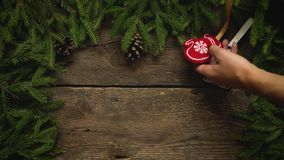 Women`s hands create a Christmas decor. Christmas tree branches with cones and christmas decorations on wooden texture stock video footage