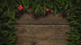 Women`s hands create a Christmas decor. Christmas tree branches with cones and christmas decorations on wooden texture stock footage