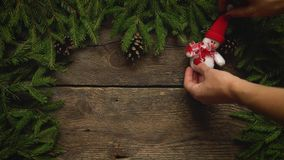 Women`s hands create a Christmas decor. Christmas tree branches with cones and christmas decorations on wooden texture stock video