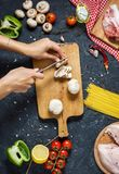 Women`s hands cut into mushrooms. Pasta ingredients. Chicken breasts, Cherry tomatoes, spaghetti pasta and mushrooms on the dark royalty free stock photos