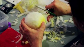 Women`s hands cut with scissors the foam for toys giving it a round shape.