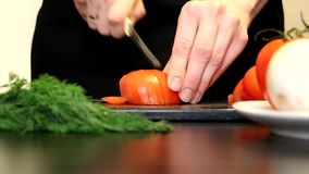 Women`s hands cut tomato stock footage